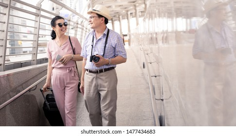 Senior Asian couple with a woman dragging a suitcase and talking happily with smiling at the airport to prepare to travel. Happiness of aunts and uncles in traveling travel together with smile.
