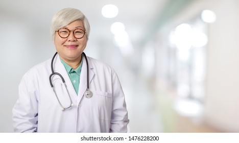 Senior Asian doctor woman with smiling  face on the background of the modern hospital