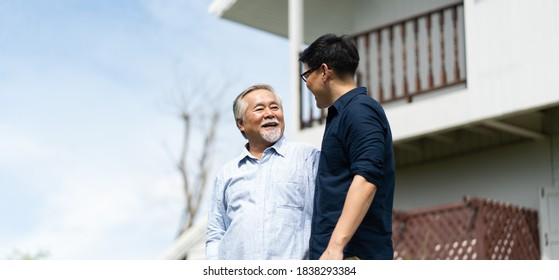 Senior Asian Father With Adult grown Son hugging outdoors.