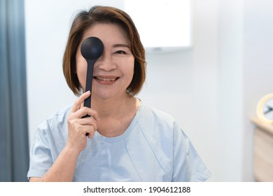 Senior Asian female patient holding  occluder to covering one eye to check her vision