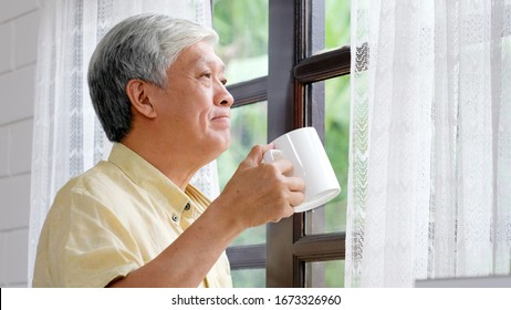 Senior asian man drinking coffee while standing by window in the morning, Happy elderly asia male holding coffe cup at home, Retirement old people healthy lifestyle