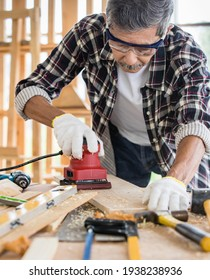 Senior Asian man in goggles and gloves polishing timber board on table while working in professional workshop, old aged hobby afer retired concept.