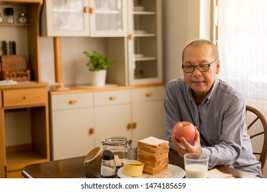Senior asian man hands holding red apple fresh fruit at home,Elderly healthy food concept