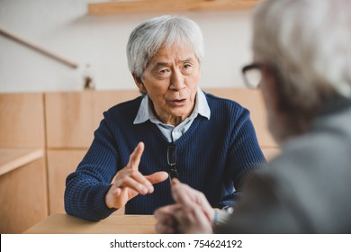 senior asian man having discussion with friend