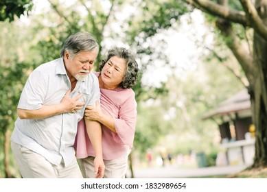 Senior Asian Man hält seine Brust und fühlt Schmerzen an Herzinfarkt, während seine Frau Unterstützung und Hilfe im Freien im Park leistet