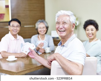 senior asian man looking at camera smiling while playing cards with friends.