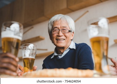 senior asian man sitting in bar with friends and drinking beer