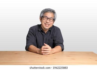 The senior Asian man sitting at the desk.