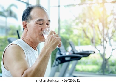 Senior Asian Man Smiling Face Drinking Water from Glass in Hand After Workout in Fitness - Health Care, Sport, Lifestyle Concept