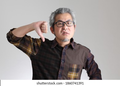 The senior Asian man standing on the white background
