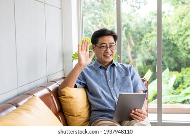 Senior Asian men smile and feeling happy while using smartphone tablet for video call with his family. Internet wireless technology with retirement person at home.