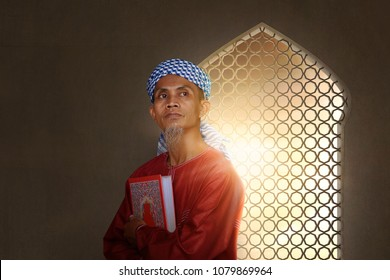 Senior asian muslim man carrying holy book of muslims on the mosque
