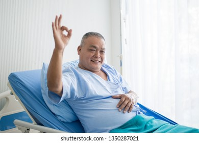 Senior Asian patient making an OK hand sign showing been recovery from sickness while admitting in hospital.