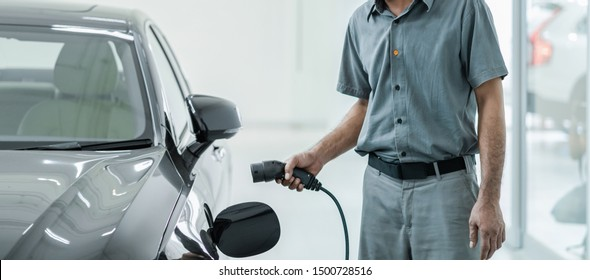 Senior asian Technician is charging the electric car or EV in service center for maintainance, Eco-friendly alternative energy concept