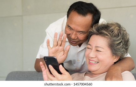 Senior Asian wife and husband use video call to son or daughter with happy smiling face. Warm family. Social distancing.