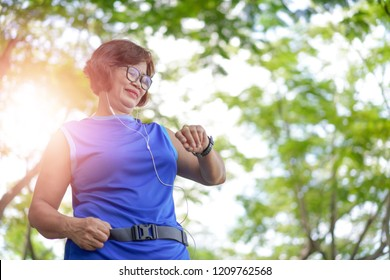 Senior asian woman checking time from smart watch. Checking heart rate while jogging in the park. Looking on smartwatch her heartbeat while running