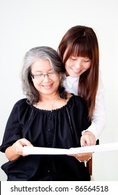 senior asian woman enjoy reading with her granddaughter
