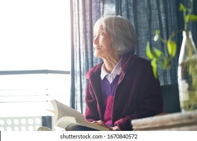 senior Asian woman reading a book at home enjoying retirement