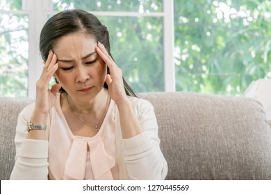 Senior Asian woman sitting on the sofa and having an headache indoors.