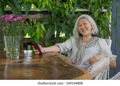Senior asian woman sitting at the table and surfing the Web. Smiling in camera. Green Cafe interior, technology background. Text space