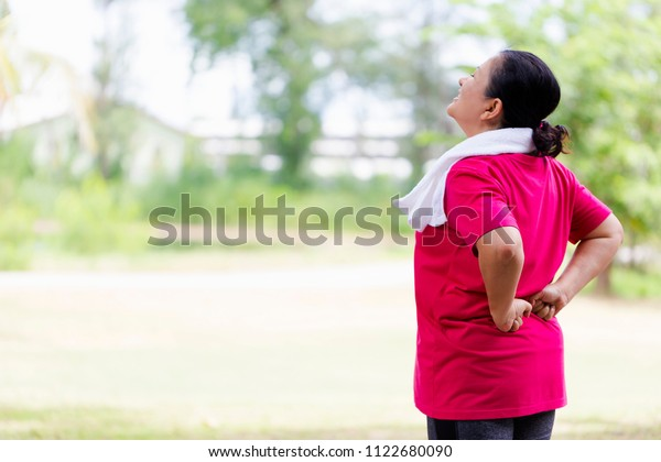 Senior Asian woman suffering from backache while exercise on park outdoors. Mature woman with backache,Lower back pain. people ,health care or medical and lifestyle concept