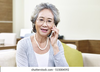senior asian woman talking on cellphone, appears to be disappointed, upset and unhappy