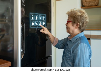 A senior asian woman is touching control panel of display on smart futuristic refrigerator