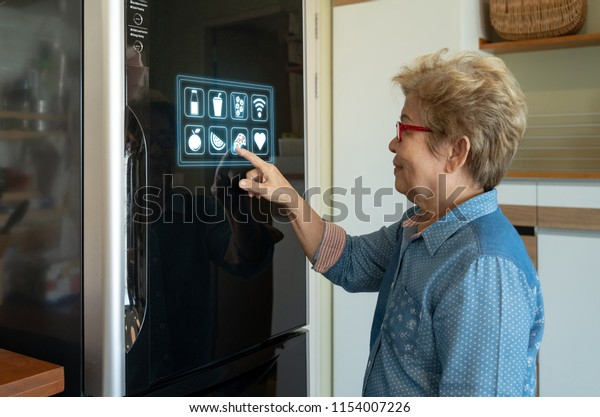 A senior asian woman is touching control panel of display on smart futuristic 