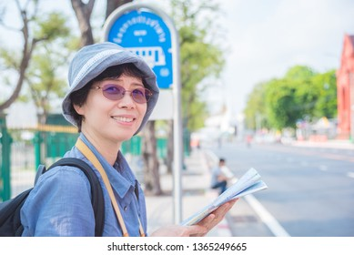 Senior asian woman tourist holding a paper map traveling in Bangkok,Thailand.