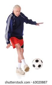 A senior athlete kicking a soccer ball.  Isolated on white.