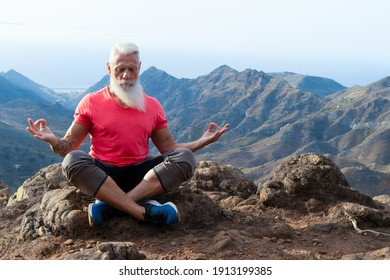 Senior Athlet Mann mit weißem Bart und Tattoo Gruß Sonnenaufgang und meditierend, gedankenvolles Leben und gesundes Wohlbefinden Konzept
