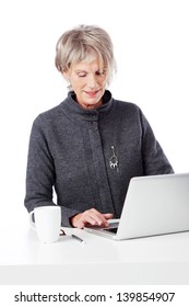 Senior attractive female office worker seated at a white desk using a laptop computer against a white background