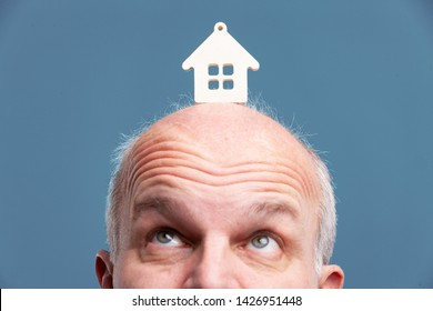 Senior balding man looking up at a model house balanced on his forehead in a close up cropped view of his eyes isolated on blue on a conceptual image