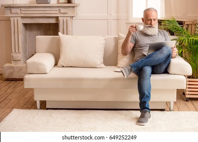 senior bearded man drinking coffee and looking on laptop while sitting on sofa at home