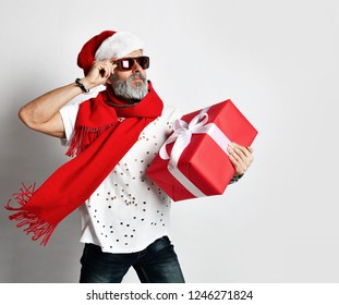 Senior bearded man in Santa Claus hat holding red gift box over grey background looking at the corner wishes Merry Christmas and a happy new year 2019