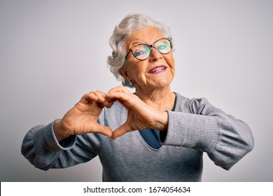 Senior beautiful grey-haired woman wearing casual sweater and glasses over white background smiling in love showing heart symbol and shape with hands. Romantic concept.
