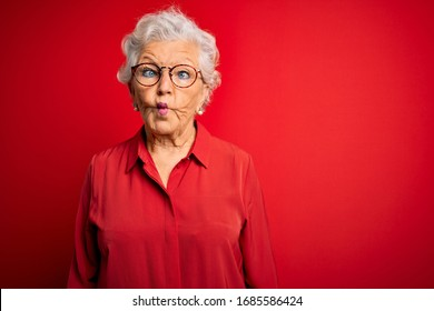 Senior beautiful grey-haired woman wearing casual shirt and glasses over red background making fish face with lips, crazy and comical gesture. Funny expression.