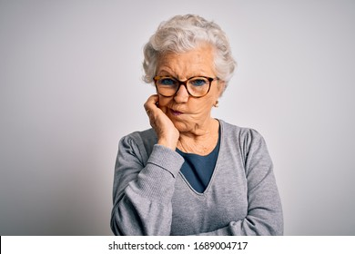 Senior beautiful grey-haired woman wearing casual sweater and glasses over white background thinking looking tired and bored with depression problems with crossed arms.