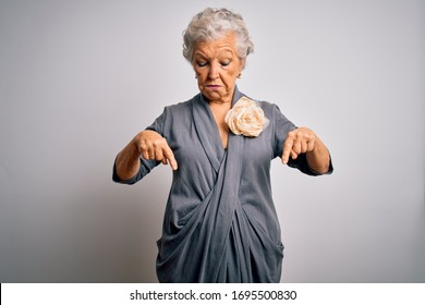 Senior beautiful grey-haired woman wearing casual dress standing over white background Pointing down looking sad and upset, indicating direction with fingers, unhappy and depressed.