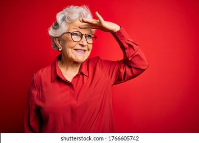 Senior beautiful grey-haired woman wearing casual shirt and glasses over red background very happy and smiling looking far away with hand over head. Searching concept.