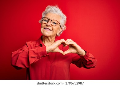 Senior beautiful grey-haired woman wearing casual shirt and glasses over red background smiling in love doing heart symbol shape with hands. Romantic concept. - Shutterstock ID 1796752987