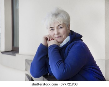 Senior beautiful lady with blond hair is looking toward viewer.