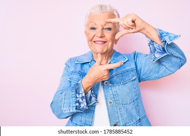 Senior beautiful woman with blue eyes and grey hair wearing casual denim jacket smiling making frame with hands and fingers with happy face. creativity and photography concept.