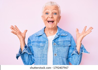 Senior beautiful woman with blue eyes and grey hair wearing casual denim jacket celebrating victory with happy smile and winner expression with raised hands