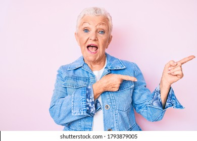 Senior beautiful woman with blue eyes and grey hair wearing casual denim jacket smiling and looking at the camera pointing with two hands and fingers to the side.