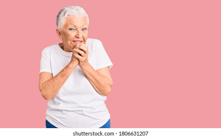 Senior beautiful woman with blue eyes and grey hair wearing casual white tshirt laughing nervous and excited with hands on chin looking to the side