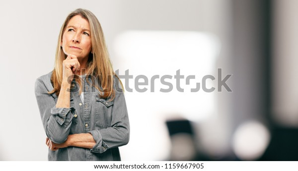 Senior schöne Frau Mit einem verwirrten und nachdenklichen Blick, nach der Seite, Denken und Wunder zwischen verschiedenen Optionen.