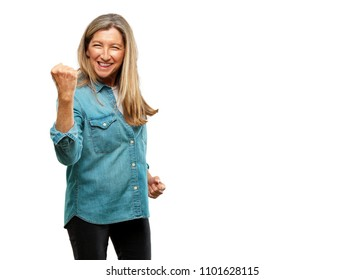 senior beautiful woman gesturing victory, with a happy, proud and satisfied look on face and holding arm  with fist pressed, showing strength or success, celebrating an achievement.