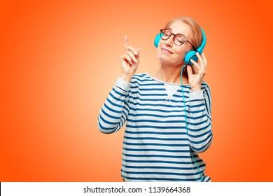 senior beautiful woman listening music with a headphones