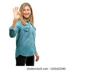 "senior beautiful woman making an ""alright"" or ""okay"" gesture approvingly with hand, looking happy and satisfied, with a broad smile. Positive check sign. Lateral or side view."